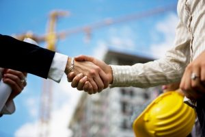 Construction manager and contractor shaking hands